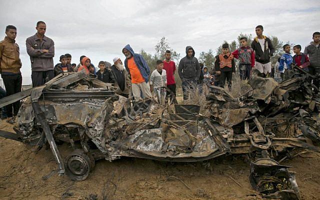 Los palestinos están parados junto a los restos de un automóvil presuntamente usado por las fuerzas especiales israelíes durante una redada en Gaza, que luego fue destruido en un ataque aéreo israelí, en Khan Younis en el sur de la Franja de Gaza el 12 de noviembre de 2018. (Dijo KHATIB / AFP )
