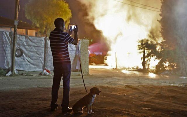 Un hombre mira un edificio que fue incendiado luego de ser alcanzado por un cohete lanzado desde la Franja de Gaza, en la ciudad de Sderot, sur de Israel, el 12 de noviembre de 2018. (Menahem KAHANA / AFP)
