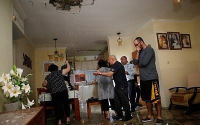 Los israelíes inspeccionan los daños en un apartamento que fue alcanzado por un cohete disparado desde la Franja de Gaza, en la ciudad de Ashkelon, al sur de Israel, el 12 de noviembre de 2018. (Gil Cohen-Magen / AFP)