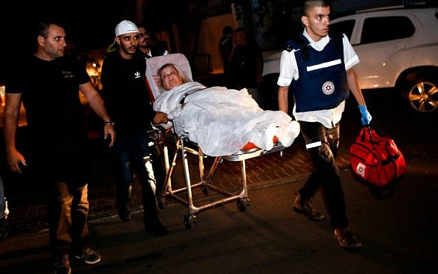 Una mujer lesionada israelí, evacuada de su apartamento que fue incendiado después de ser golpeado por un cohete disparado desde la franja de Gaza, es escoltada al hospital en una camilla, en la localidad israelí del sur de Ashkelon el 12 de noviembre de 2018. (GIL COHEN-MAGEn/AFP)