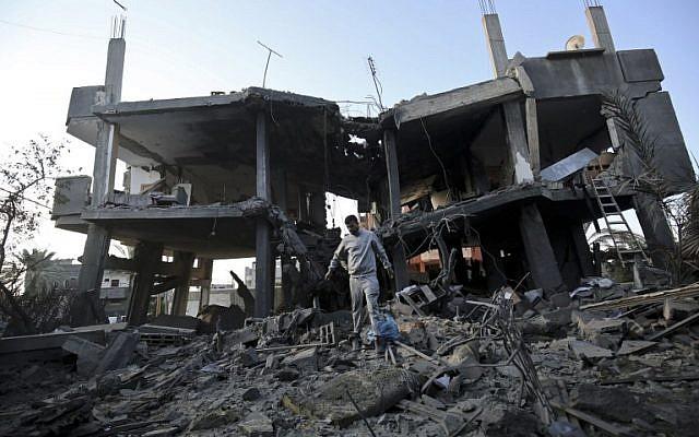 Palestinos caminan entre escombros de un edificio que fue destruido en un ataque aéreo israelí en Khan Yunis en el sur de la Franja de Gaza el 13 de noviembre de 2018. (Dijo KHATIB / AFP)