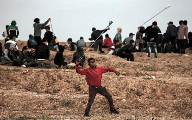 Un manifestante palestino usa una honda para arrojar piedras hacia las fuerzas israelíes durante una protesta el 16 de noviembre de 2018, en las afueras del este de la ciudad de Gaza, cerca de la frontera con Israel. (Foto por MAHMUD HAMS / AFP)