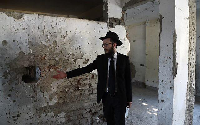 El rabino Israel Kozlovsky, el director de la casa de Nariman Chabad, señala gestos de esquirlas que se dejaron en el mismo estado después de los ataques terroristas de 2008, durante una visita a los medios en la víspera del décimo aniversario de los ataques en Mumbai el 25 de noviembre de 2018 ( PUNIT PARANJPE / AFP)