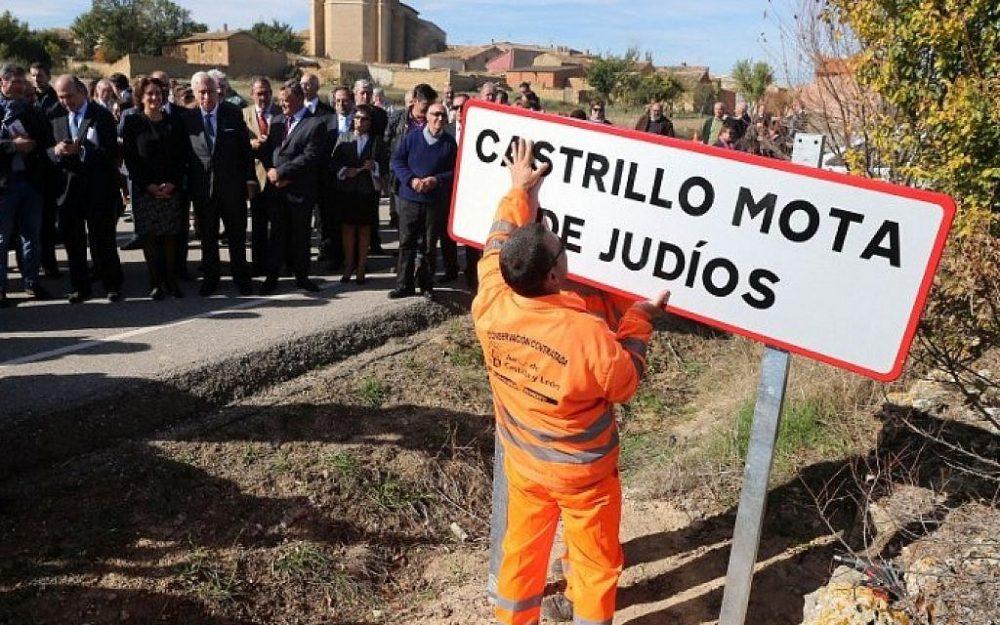 Los funcionarios observan a un empleado que está colocando una señal de tráfico que lee el nuevo nombre del pueblo español 'Castrillo Mota de Judios' que significa 'Montículo de judíos de Castrillo' en la entrada de Castrillo Mota de Judios, cerca de Burgos el 23 de octubre de 2015 (AFP FOTO / CESAR MANSO)