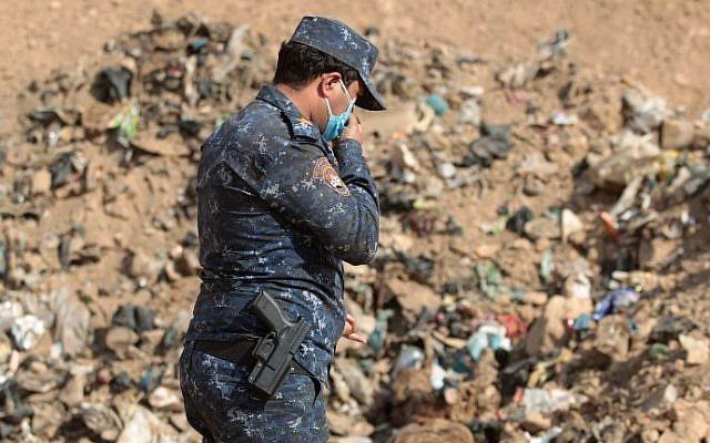 Un miembro de las fuerzas iraquíes revisa una fosa común en Hamam al-Alil el 7 de noviembre de 2016, luego de que recobraron el área de los jihadistas del Estado Islámico durante la operación para retomar Mosul. (AHMAD AL-RUBAYE / AFP)