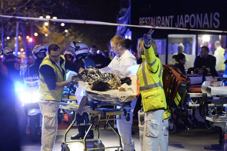 Los rescatistas evacuan a una persona lesionada cerca de la sala de conciertos de Bataclan en el centro de París, a principios del 14 de noviembre de 2015. (AFP PHOTO / MIGUEL MEDINA)