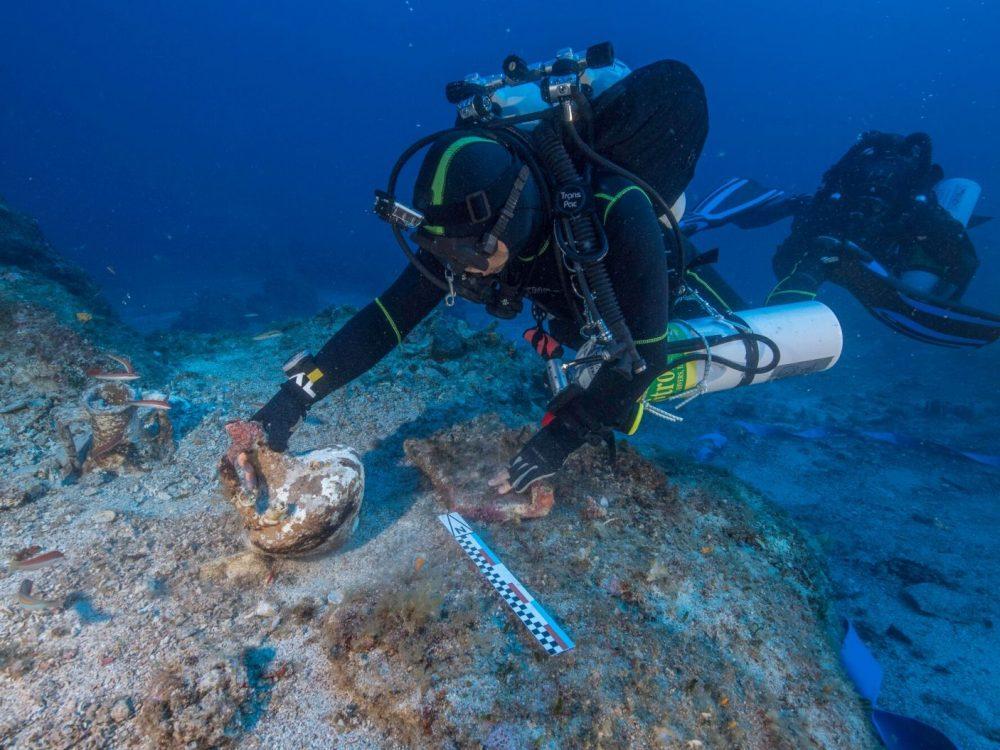 Buceador que levanta ánfora que posiblemente contenía vino o perfume del naufragio de Antikythera Brett Seymour