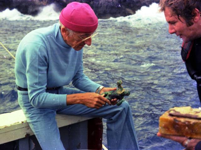 Jacques Cousteau mira una estatuilla de bronce rescatada de EUA