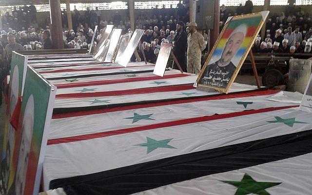 En esta foto publicada por la agencia de noticias oficial siria SANA, los dolientes de la comunidad drusa asisten a un funeral masivo de personas asesinadas el día anterior por una serie de atentados suicidas lanzados por combatientes del Estado Islámico en el campo este y norte de la provincia sur de Al-Sweida, Siria, el 26 de julio de 2018. (SANA a través de AP)