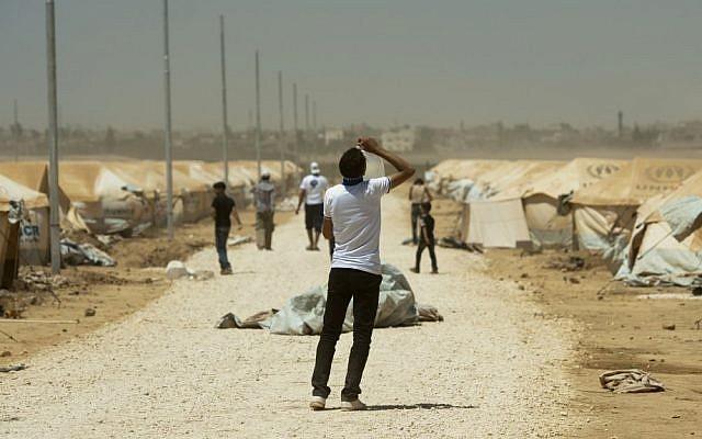 Un refugiado sirio bebe agua en el campamento de refugiados de Zaatari en Jordania, 13 de agosto de 2012. (Crédito de la foto: AP / Clemens Bilan)