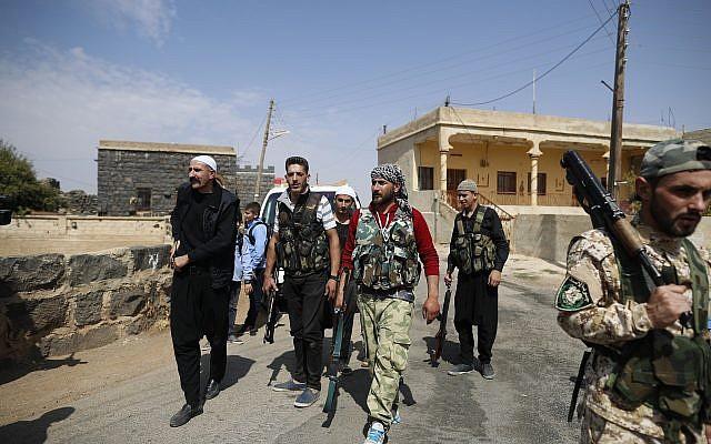 En esta foto del 4 de octubre de 2018, hombres armados drusos, que portan armas para defender su aldea del ataque del Estado Islámico, patrullan la aldea de Rami en la provincia sureña de Sweida, Siria. (Foto AP / Hassan Ammar)