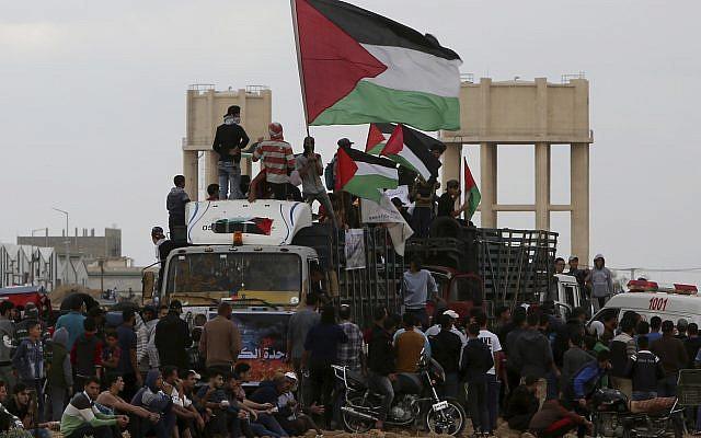 Ilustrativo: Los palestinos ondean banderas mientras viajan en un camión lleno con neumáticos cerca de la frontera de la Franja de Gaza con Israel al este de la ciudad de Gaza, viernes 26 de octubre de 2018. (AP / Adel Hana)