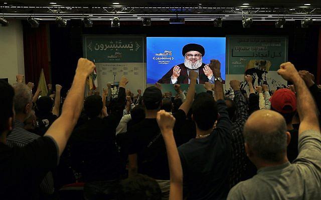 El partidario del grupo terrorista Hezbollah respaldado por Irán levanta sus puños y aplaude mientras escuchan un discurso del líder de Hezbollah, Hassan Nasrallah, a través de un enlace de video, durante un mitin que conmemora el Día del Mártir de Hezbollah, en un suburbio del sur de Beirut, Líbano, noviembre. 10, 2018. (Foto AP / Bilal Hussein)