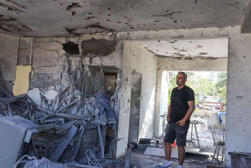 Un hombre está parado dentro de una casa que fue alcanzada por un cohete disparado desde la Franja de Gaza en la ciudad de Ashkelon, al sur de Israel, el 13 de noviembre de 2018 (Nati Shohat / Flash 90)