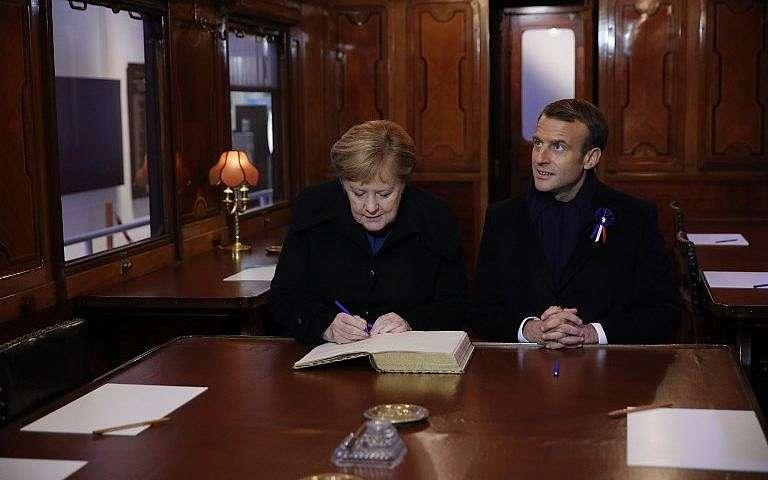 El presidente francés, Emmanuel Macron, y la canciller alemana, Angela Merkel, firman el Libro Dorado el 10 de noviembre de 2018, mientras se sientan en el vagón del tren donde se firmó el armisticio que terminó la Guerra Mundial en el claro de Rethondes (el Claro del Armisticio) en Compiegne, norte Francia.(Philippe Wojazer / Pool / AFP)