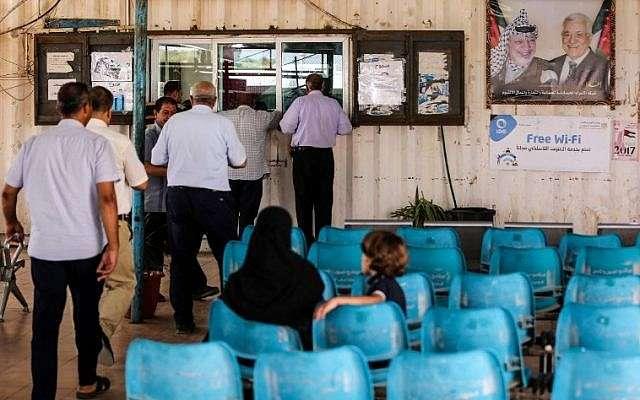 Árabes esperan mientras otros presentan documentos de viaje a los oficiales de la Autoridad Palestina en el cruce de Erez con Israel cerca de Beit Hanoun en el norte de la Franja de Gaza el 27 de agosto de 2018. (AFP Photo / Mahmud Hams)