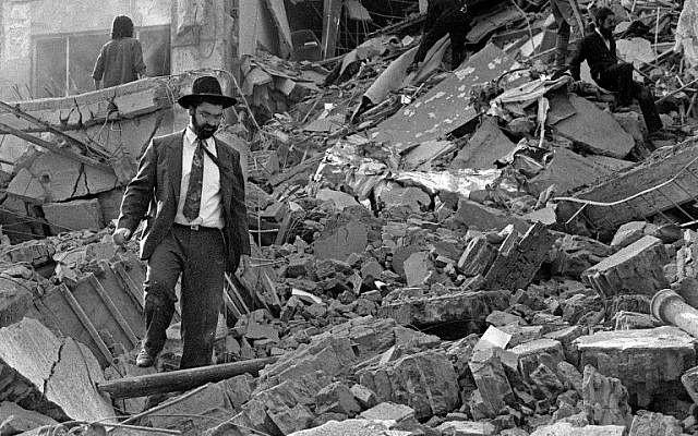 Un hombre camina sobre los escombros después de que explotara una bomba en la Asociación Mutual Israelita Argentina (AMIA) en Buenos Aires, Argentina, 18 de julio de 1994. (AFP / Ali Burafi)
