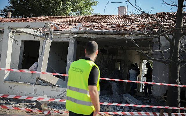 Las personas se reúnen frente a una casa que fue alcanzada por un cohete disparado desde la Franja de Gaza en la ciudad de Ashkelon, al sur de Israel, el 13 de noviembre de 2018 (Hadas Parush / Flash90)