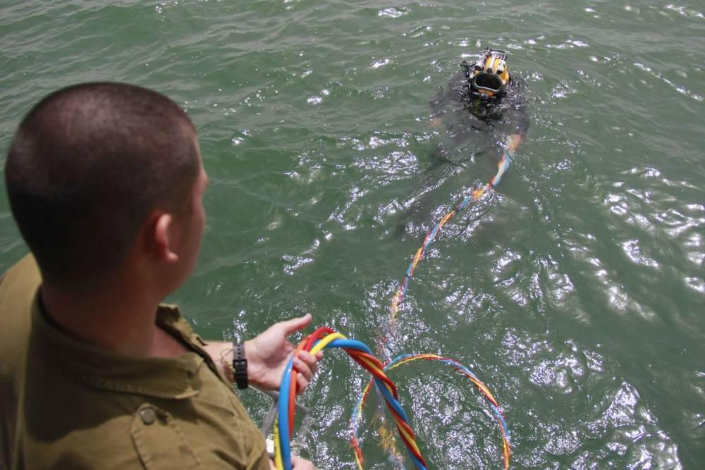 Soldados de Israel tamizan a través del lodo del fondo del Mar de Galilea como parte de una búsqueda del teniente Yakir Naveh, cuyo avión se estrelló en 1962. (Fuerzas de Defensa de Israel)