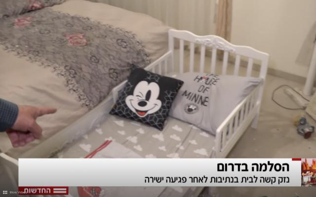 El reportero de Hadashot TV Moshe Nussbaum apunta a una cuna en una habitación donde un trozo de metralla de un cohete de Hamas entró en una casa en Netivot, 12 de noviembre de 2018 (noticias de Hadashot TV)