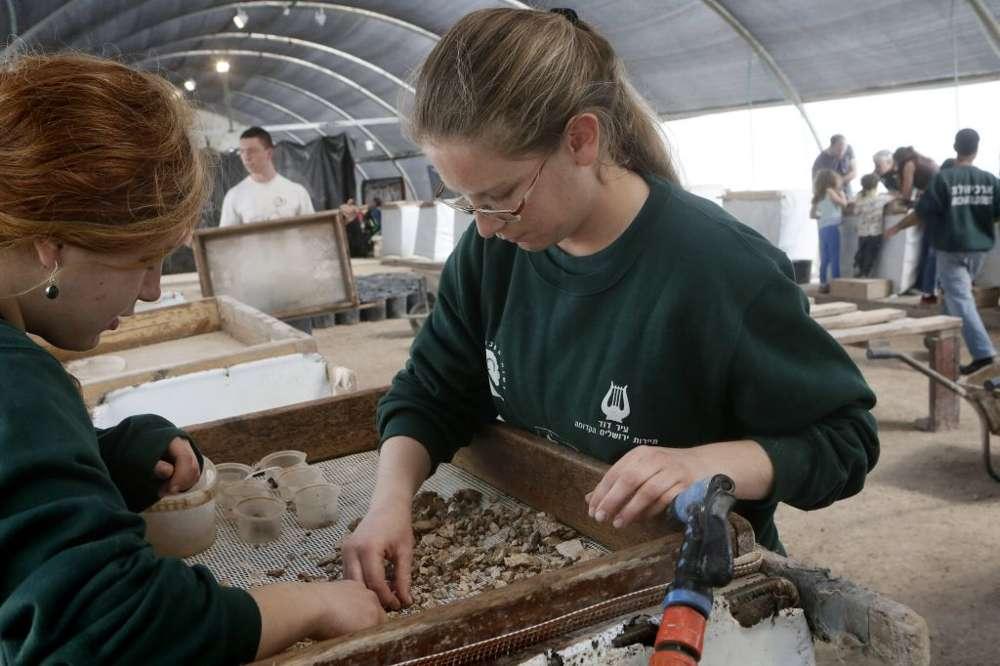 Voluntarios y empleados escogen los hallazgos en el Proyecto de Tamizado del Monte del Templo en Emek Tzurim, ubicado en el Monte de los Olivos, cerca de la Ciudad Vieja de Jerusalem el 10 de marzo de 2014. (Miriam Alster / Flash 90)