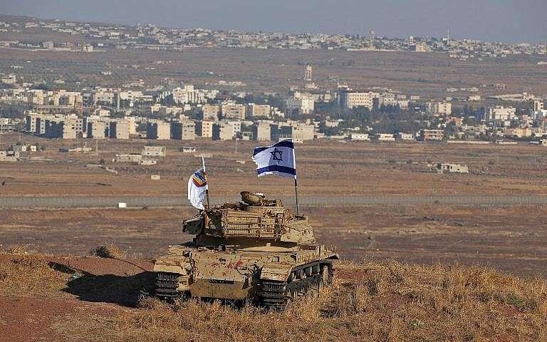 Una bandera israelí ondea sobre los restos de un tanque en una colina en los Altos del Golán que domina la frontera con Siria el 18 de octubre de 2017. (Foto de AFP / Jalaa Marey)
