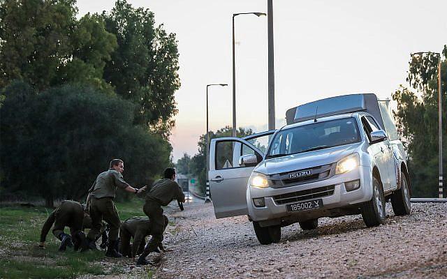 Soldados israelíes que se encuentran en el lado de la carretera en el sur de Israel mientras se protegen de los cohetes que se lanzaron desde Gaza hacia Israel, 12 de noviembre de 2018. (Hadas Parush / Flash90)