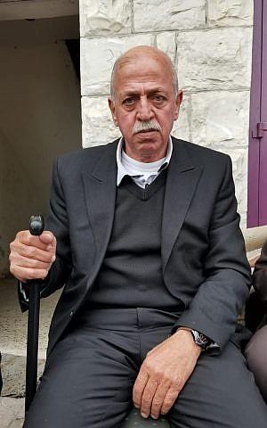 Imad Abu Asabeh sentado en la acera cerca de la Mezquita Nabi Younis en una ciudad de Cisjordania el 14 de noviembre de 2018. (Adam Rasgon / Times of Israel)