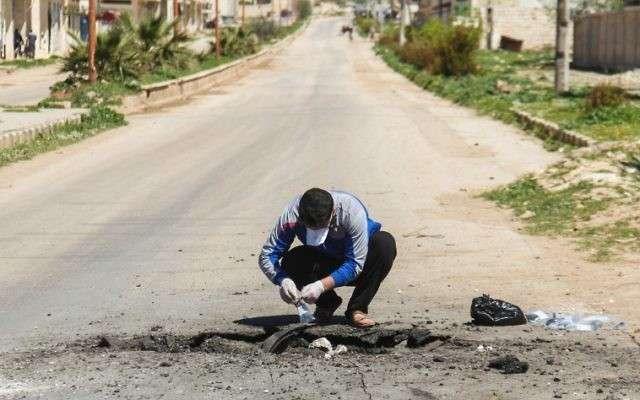 Un hombre sirio recolecta muestras del sitio de un presunto ataque con gas tóxico en Khan Sheikhoun, en la provincia de Idlib, noroeste de Siria, el 5 de abril de 2017. (AFP / Omar Haj Kadour)