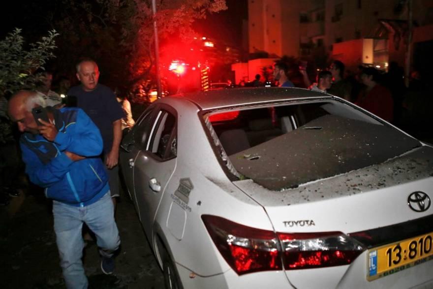 Dos hombres pasan por delante de un vehículo que fue alcanzado por un cohete disparado desde la Franja de Gaza, en la ciudad de Ashkelon, al sur de Israel, el 12 de noviembre de 2018. (GIL COHEN-MAGEN / AFP)