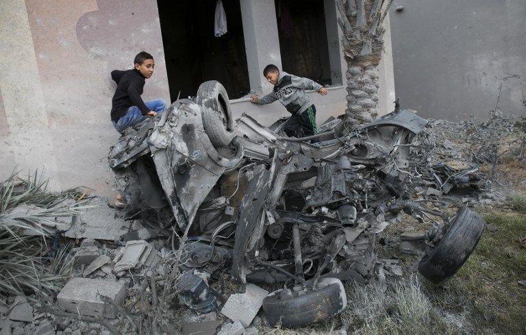 Árabes de pie junto a los restos de un automóvil, que se dice que fue destruido tras un ataque aéreo israelí en Khan Yunis, en el sur de la Franja de Gaza, el 12 de noviembre de 2018 (foto de SAID KHATIB / AFP)