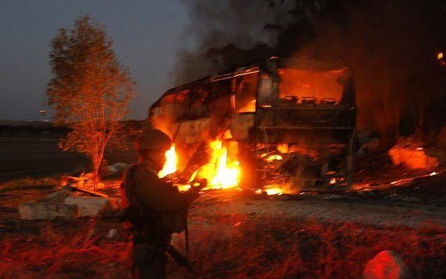 Las fuerzas de seguridad y los bomberos israelíes se reúnen cerca de un autobús incendiado después de que fue alcanzado por un misil antitanque disparado desde el enclave palestino, en la frontera entre Israel y Gaza cerca del kibbutz de Kfar Aza, el 12 de noviembre de 2018. (Foto por Menahem KAHANA / AFP)