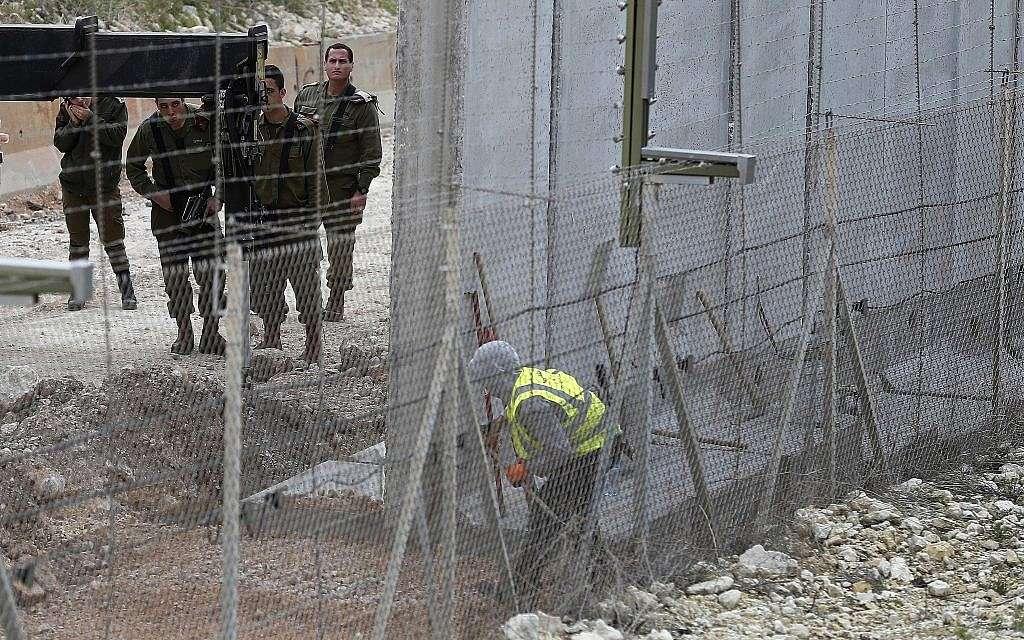 Soldados israelíes observan a un obrero de la construcción construir un muro a lo largo de la frontera israelí en la ciudad costera de Naqoura, sur del Líbano, 8 de febrero de 2018. (AP / Hussein Malla, archivo)