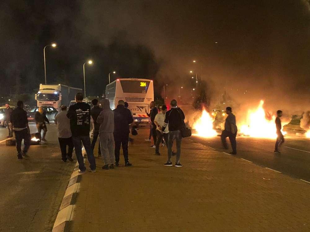 Residentes de comunidades israelíes cerca de la Franja de Gaza queman neumáticos y bloquean una carretera en la entrada a la ciudad de Sderot en protesta por un acuerdo de alto el fuego, 14 de noviembre de 2018. (Policía de Israel)