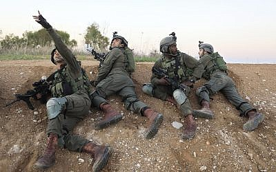 Soldados israelíes se cubren cerca de la frontera entre Israel y Gaza, 12 de noviembre de 2018. (AP Photo / Tsafrir Abayov)