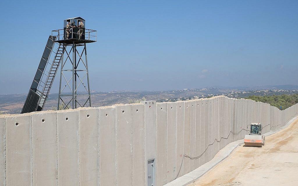 Un vehículo de construcción israelí conduce por un muro de hormigón que se está construyendo a lo largo de la 'Línea Azul' que separa a Israel y el Líbano, mientras miembros de las Fuerzas Armadas Libanesas observan desde una torre de vigilancia, cerca de la ciudad israelí de Rosh Hanikra el 5 de septiembre de 2018. (Judah Ari Gross / tiempos de Israel)