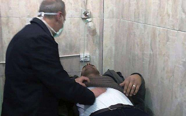 La foto publicada por la agencia de noticias oficial siria SANA muestra a un hombre que recibe tratamiento en un hospital luego de un presunto ataque químico en su ciudad de al-Khalidiya, en Aleppo, Siria, el sábado 24 de noviembre de 2018. (SANA vía AP)