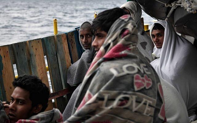 Los migrantes se sientan a bordo de MV Aquarius, un barco de rescate fletado por SOS-Mediterranee y Doctors Without Borders (MSF), en el mar Mediterráneo entre Libia e Italia el 9 de mayo de 2018. (AFP PHOTO / LOUISA GOULIAMAKI)