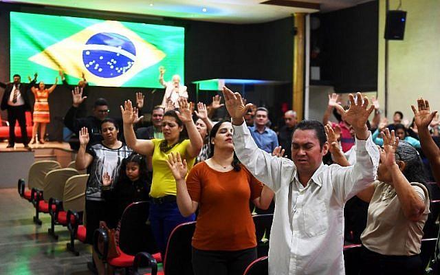ARCHIVO - En esta foto tomada el 21 de septiembre de 2018, los fieles rezan en una iglesia evangélica en Brasilia por la recuperación del candidato presidencial brasileño de derecha Jair Bolsonaro, quien sufrió un ataque con un cuchillo durante un mitin de campaña (AFP PHOTO / EVARISTO SA)
