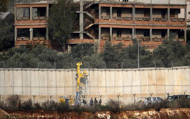 Soldados israelíes de pie junto a la maquinaria de excavación cerca del muro fronterizo con el Líbano en el área de Metulla, 4 de diciembre de 2018. (JALAA MAREY / AFP)