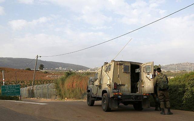 Esta fotografía tomada el 4 de diciembre de 2018 cerca de la ciudad de Metula, en el norte de Israel, muestra a soldados israelíes de pie frente a un vehículo militar cerca de la frontera con el Líbano. (JALAA MAREY / AFP)