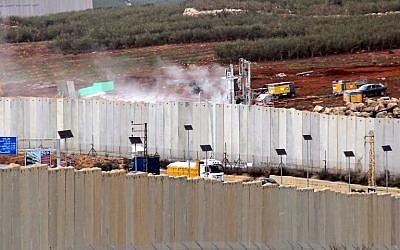 Esta fotografía tomada el 4 de diciembre de 2018, desde la aldea sur de Líbano, Kfar Kila, muestra una vista de la maquinaria israelí que opera detrás del muro fronterizo en Israel (R). (Ali DIA / AFP)