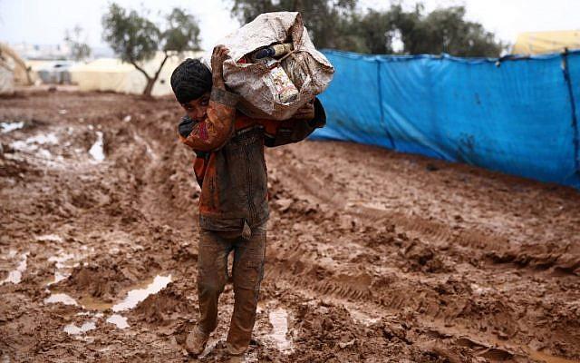 Un niño sirio carga un saco en su hombro mientras camina en el lodo en un campamento de desplazamientos en las afueras de Shamarin, cerca de la frontera con Turquía en la provincia norteña de Aleppo, el 6 de diciembre de 2018. (Nazeer AL-KHATIB / AFP)