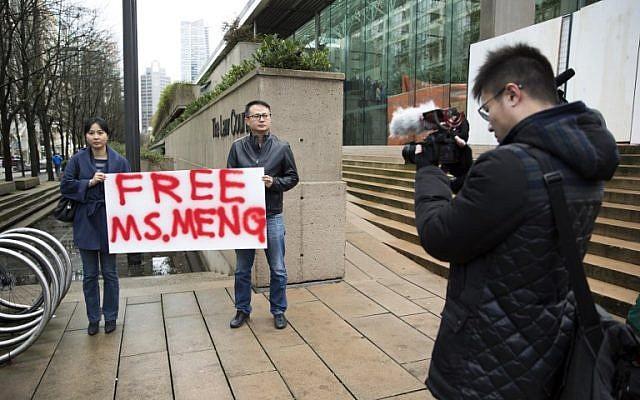 Ada Yu, a la izquierda, de Vancouver y un hombre que deseaba permanecer sin identificar, sostienen un letrero a favor de la liberación de la Directora Financiera de Huawei Technologies, Meng Wanzhou, fuera de su audiencia de fianza en los Tribunales Superiores de la Columbia Británica luego de su arresto en Canadá por extradición a los EE. UU. en Vancouver, Columbia Británica, el 10 de diciembre de 2018. (Jason Redmond / AFP)