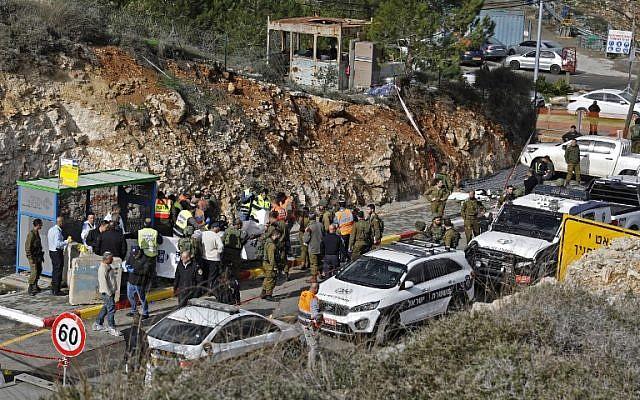 Las fuerzas de seguridad israelíes y los expertos forenses inspeccionan la escena de un tiroteo terrorista en el exterior del asentamiento de Givat Asaf, al noreste de la ciudad cisjordana de Ramallah, el 13 de diciembre de 2018. (Ahmad Gharabli / AFP)