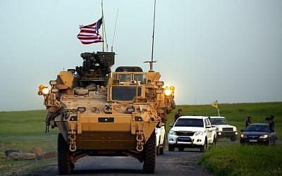 Las fuerzas estadounidenses, acompañadas por combatientes de las Unidades de Protección del Pueblo Kurdo (YPG), conducen sus vehículos blindados cerca de la aldea siria de Darbasiyah, en la frontera con Turquía, 28 de abril de 2017. (Delil Souleiman / AFP)
