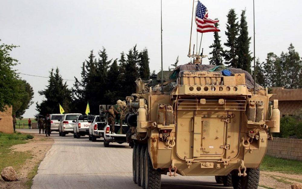 En esta foto del 28 de abril de 2017, las fuerzas estadounidenses, acompañadas por combatientes de las Unidades de Protección de los Pueblos Kurdos (YPG), conducen sus vehículos blindados cerca del pueblo sirio de Darbasiyah, en la frontera con Turquía. (Delil Souleiman / AFP)