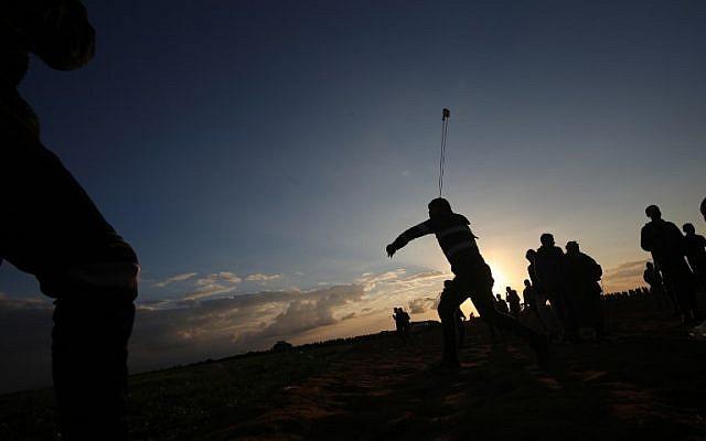 Un manifestante palestino usa una honda para arrojar piedras durante una manifestación cerca de la frontera entre Israel y Khan Yunis en el sur de la Franja de Gaza, el 21 de diciembre de 2018. (Said Khatib / AFP)