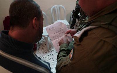 Un soldado de las FDI le notifica a un familiar del sospechoso de terrorismo Ashraf Na'alowa la intención del ejército de demoler su casa, 15 de octubre de 2018. (Unidad de Portavoces de las FDI)