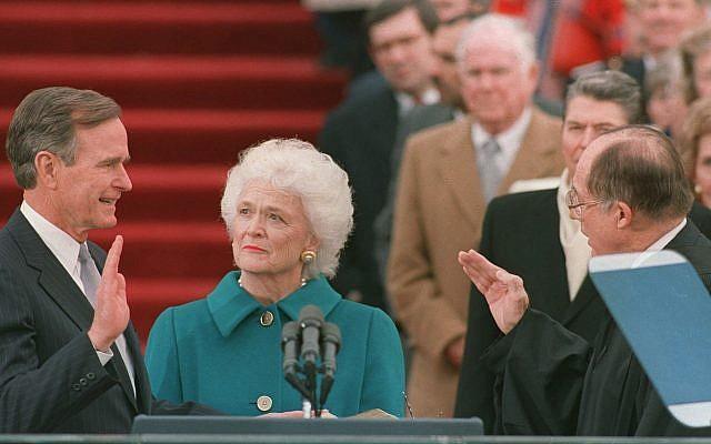 En esta foto de archivo del 20 de enero de 1989, el presidente George HW Bush levanta su mano derecha cuando toma posesión de su cargo como presidente número 41 de los Estados Unidos por el presidente William Rehnquist, frente al frente oeste del Capitolio, como primera dama Barbara Bush sostiene la biblia para su esposo (Foto AP / Bob Daugherty, Archivo)